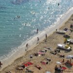 People play and sunbathing on the beach at Puerto Portals Majorca