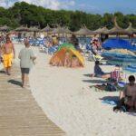 Beach walkway and bathers in Sa Coma Majorca