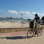 Man riding a bike on the Sa Coma promenade Majorca