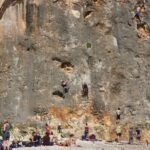 People climbing the cliffs at Cala Bota beach Majorca