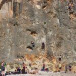 People climbing the cliffs at Cala Bota beach Majorca