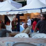 People sitting and viewing stalls at the Cala Ratjada festival Majorca