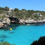 People swimming and a pedalo beneath the sea cliffs at Cala Figuera Majorca
